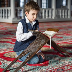 Kid reading The Holy Koran,mosque